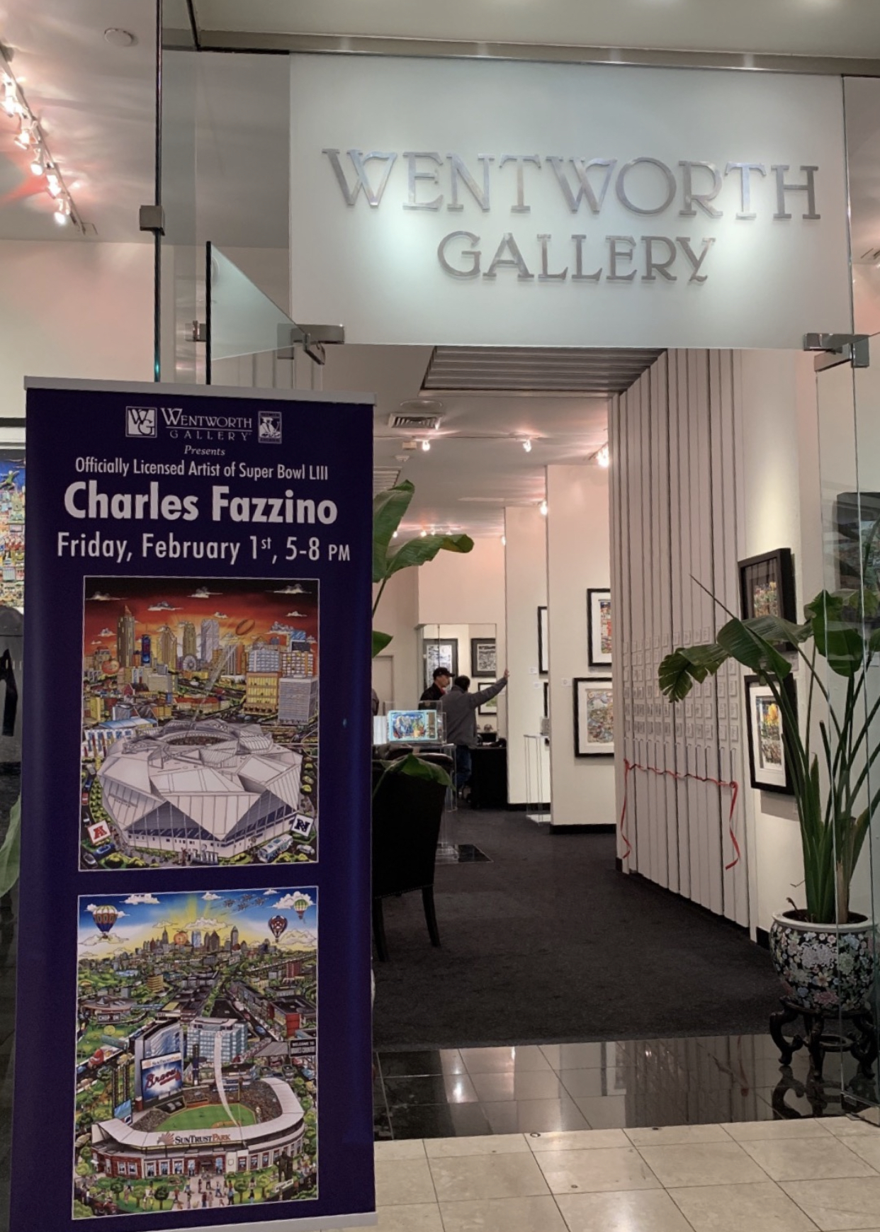 A view from outside the Wentworth Gallery looking in at artwork by Charles Fazzino