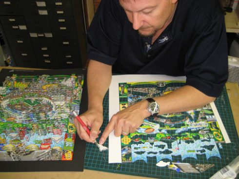 Charles Fazzino in the process of cutting out a cloud for one of his 3-D pop art pieces of a football stadium.