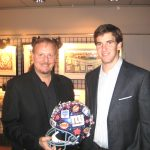 Eli Manning accepts a hand-painted helmet from Eli Manning at The Taste of the NY Giants charity event