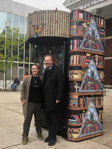 Charles and Heather Fazzino in front of a kiosk painted with books & butterflies.