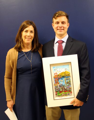 A young man, Andrew Clausen (right) is holding the Charles Fazzino Award of the Heart from Project Community Board Member Anne O'Beirne (left).