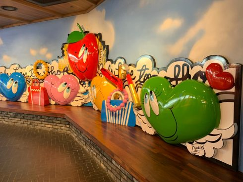 A colorful Fazzino installation behind a long bench at the mall showcasing classic Fazzino smiling hearts and an apple.