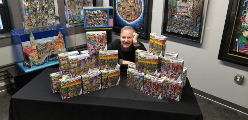 Charles Fazzino sitting at a table covered with boxes of puzzles from his new puzzle line.