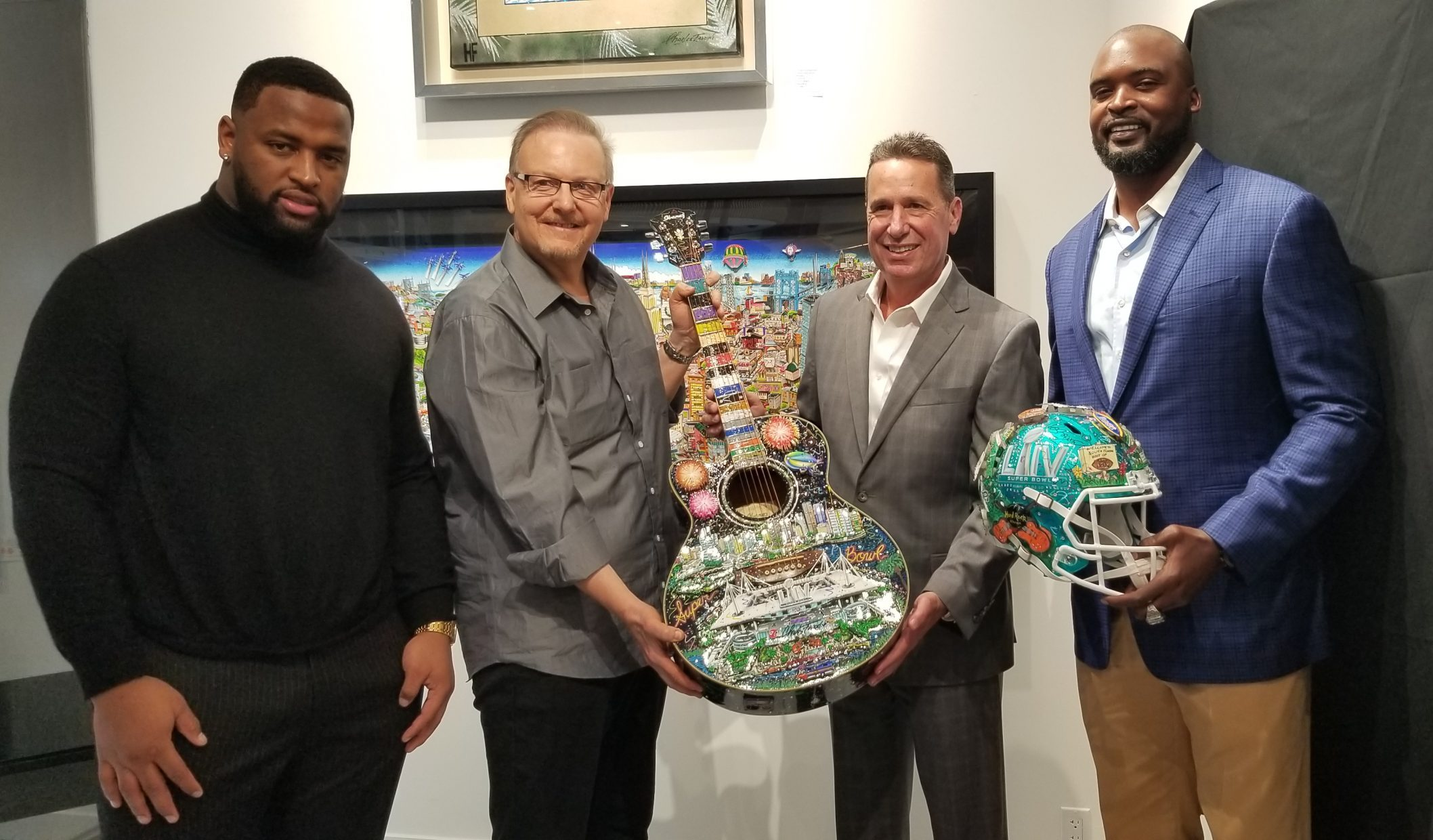 Posing with a Fazzino Super Bowl LIV guitar and helmet, from left to right: Miami Dolphin Davon Godchaux, President of the Hard Rock Hotel & Casino Bo Guidry, Former NY Giant Mathias Kiwanuka, and Charles Fazzino