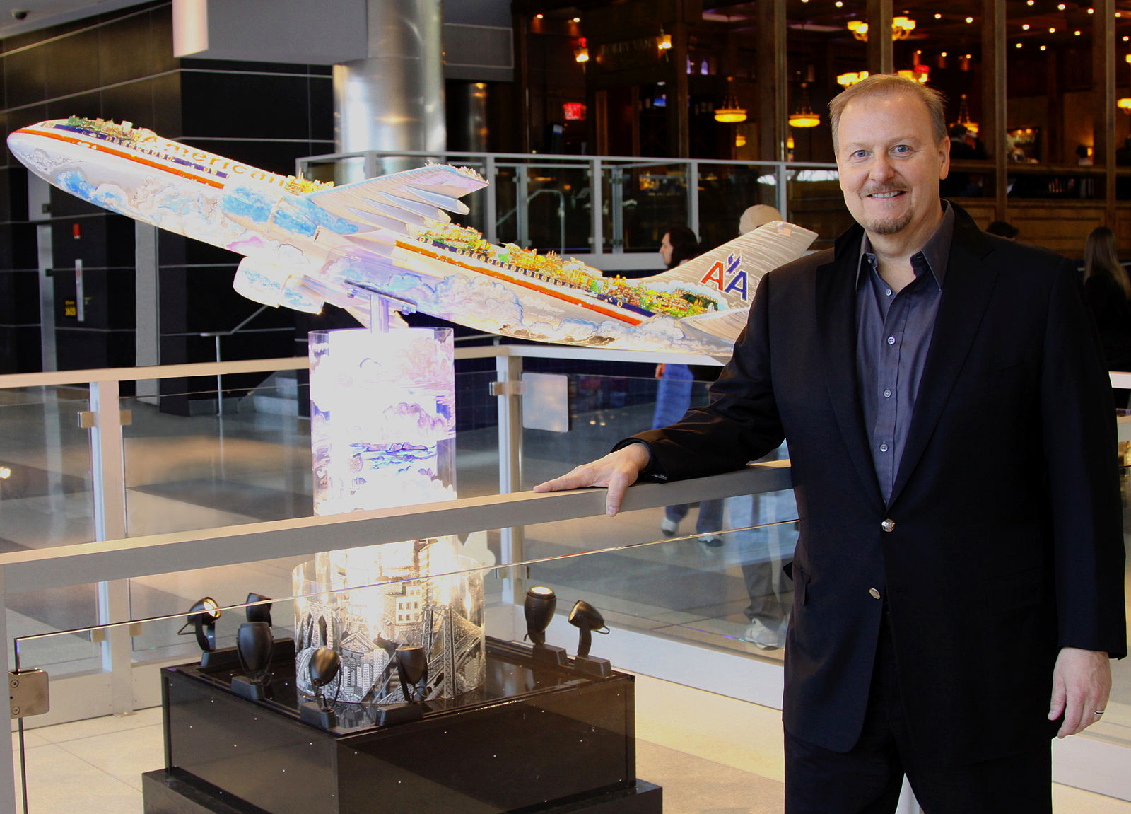 Fazzino standing next to his airplane piece at JFK Airport.