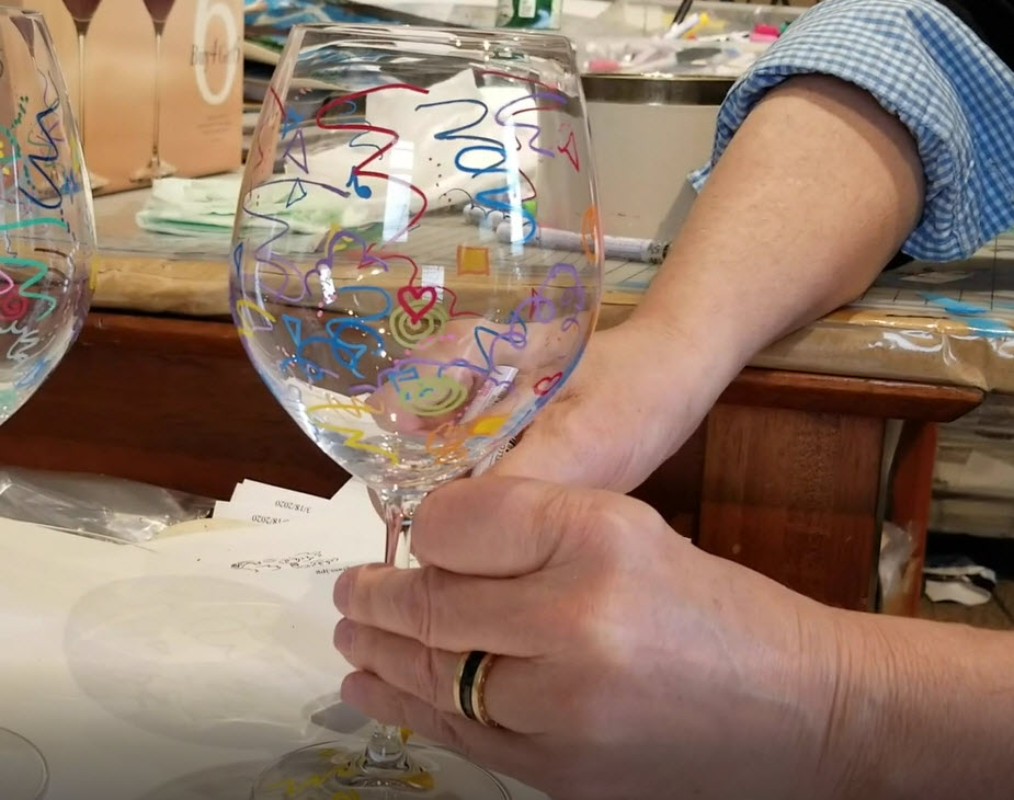 Fazzino demonstrates how to draw on a wine glass with permanent markers
