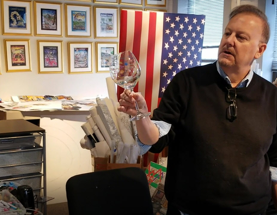 Fazzino holds up a wine glass in his art studio that has been painted with markers