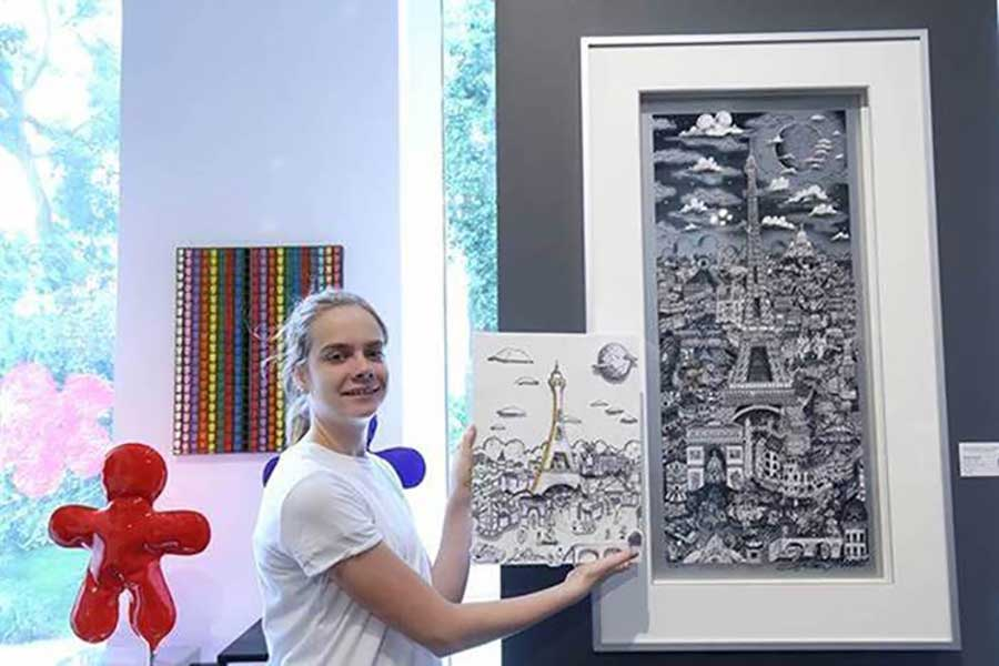 A student holds up artwork inspired by a Fazzino piece behind it from a virtual art workshop