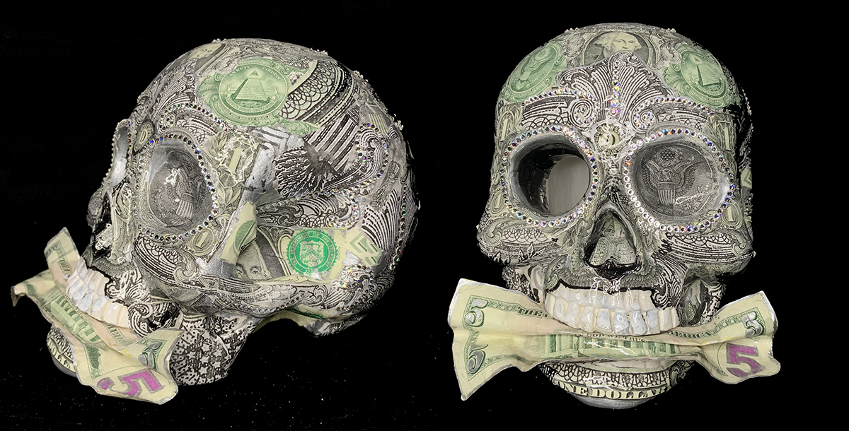 Sculpture in the shape of a skull, adorned with Swarovski crystals and a $5 bill in it's mouth