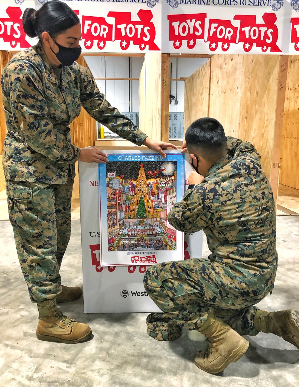 Two marines attaching Fazzino's Toys for Tots Official Poster to a donation box