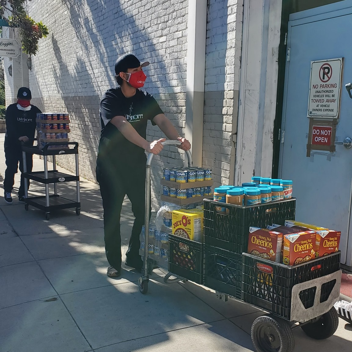 young man pushing a cart of food into building - Unity Shoppe