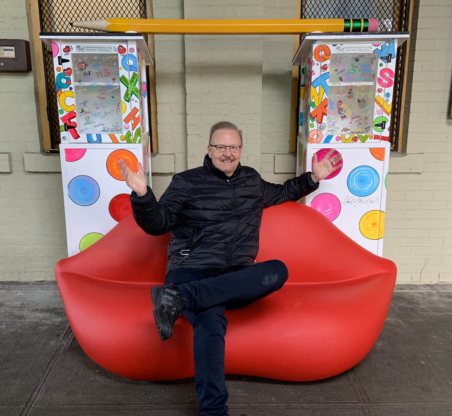 Charles Fazzino sitting on his new pop-up mini library installation at the New Rochelle train station
