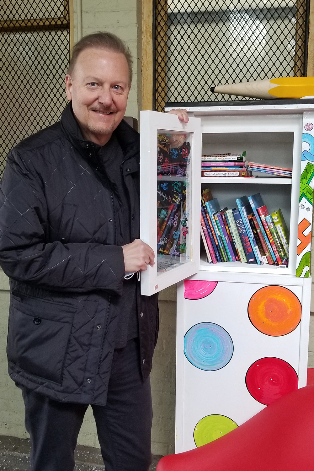 Charles Fazzino opening pop-up library kiosk door to show the wonderful amount of free books down at New Rochelle train station