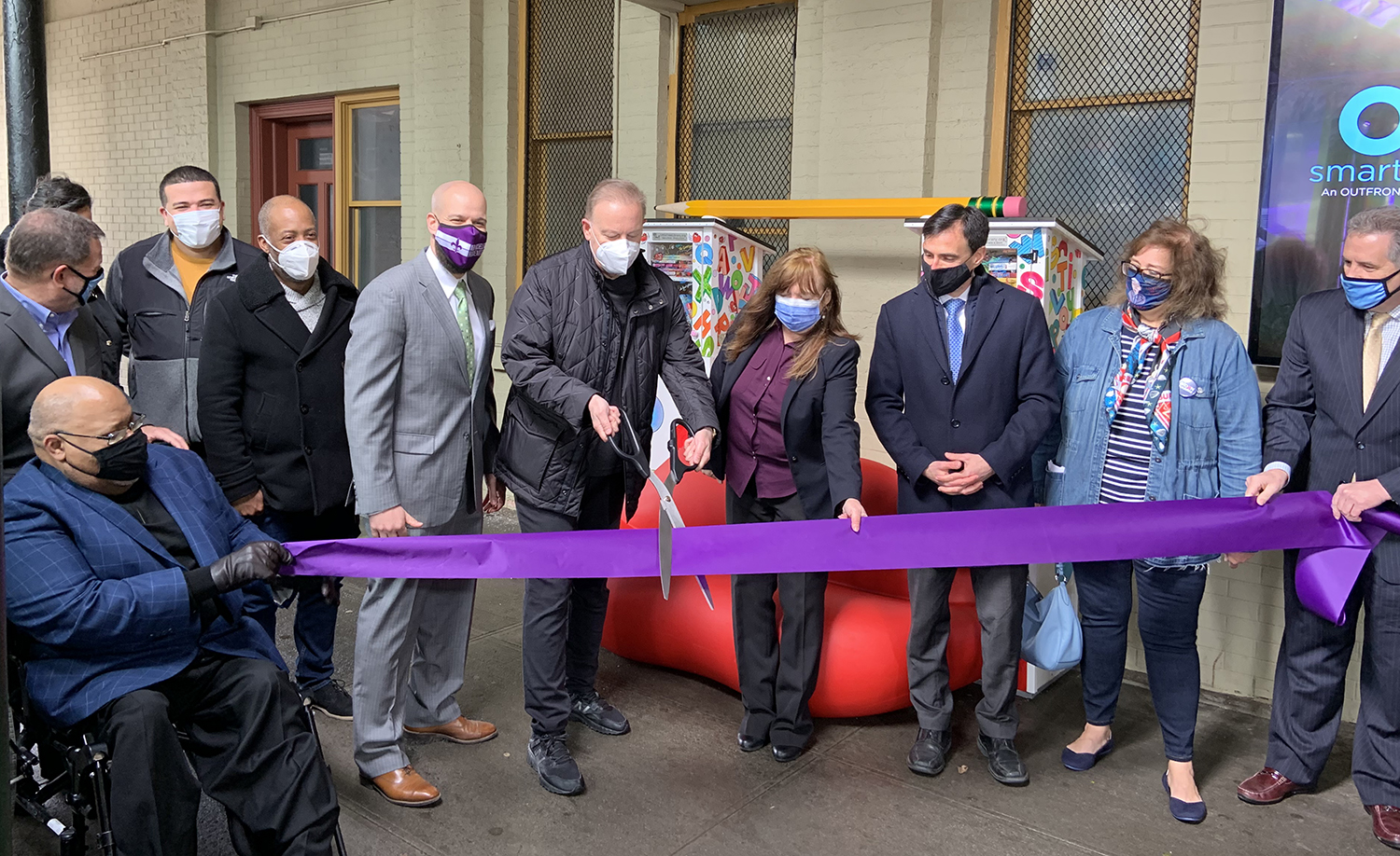 Charles Fazzino with city officials cutting a purple ribbon down at the New Rochelle Train station celebrating his new art installation