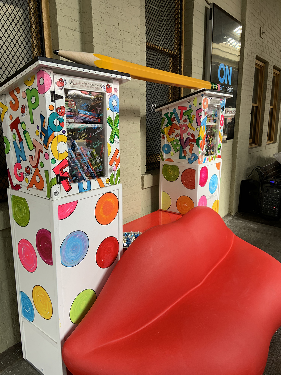 Pop-up library constructed of a pair of red lips, two mini library kiosks and a Ticonderoga pencil across the top. Charles Fazzino's pop art installation at New Rochelle train station