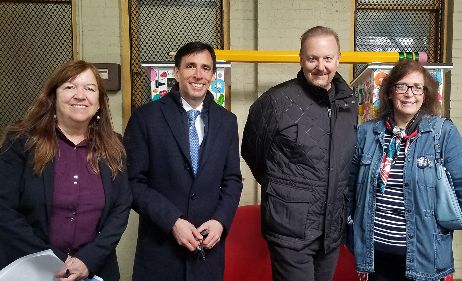 Charles Fazzino and city officials smiling in front of his latest pop art installation down at the New Rochelle train station