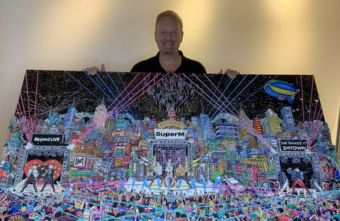 Charles Fazzino holding up 3d pop art commissioned piece for SMTOWN Museum, Seoul. Citycape of Korea with KPOP stars SUPERM front and center stage