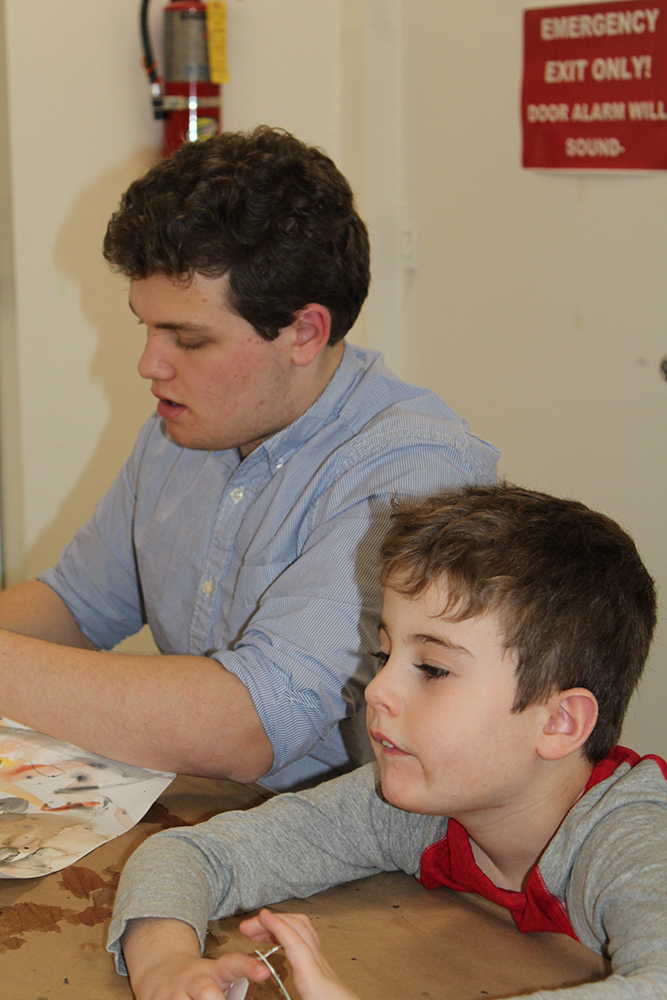 2021 Fazzino Award of Heart winner Andrew Terraciano sitting at a table doing crafts with a young boy